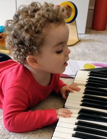 Small child playing on a toy piano