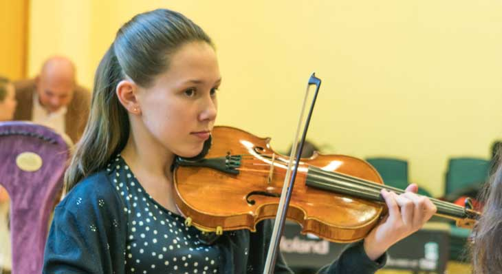 Poppy playing her violin at the Amber Trust Annual concert